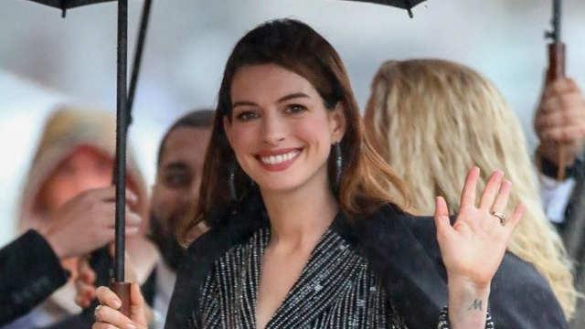 安妮·海瑟薇雨天出街 撑伞招手笑容灿烂
