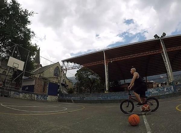 一气呵成!小伙骑小轮车压滑板将篮球从中场弹进篮筐