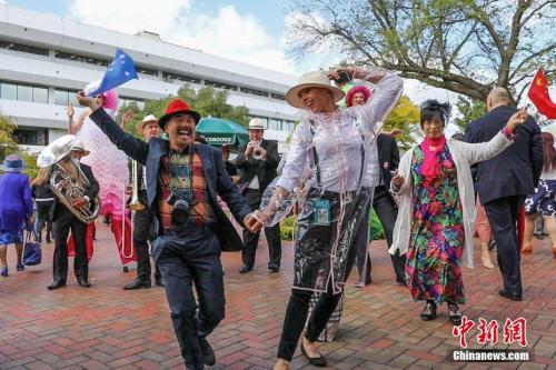 """资料图片:中国游客参加""""墨尔本赛马节""""。图为一对来自中国的夫妇伴着乐队的音乐和歌声,与一位澳大利亚工作人员共舞。<a target='_blank' href='http://www.chinanews.com/'>中新社</a>记者 陶社兰 摄"""
