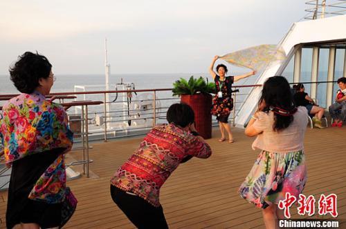 资料图片:游客在邮轮甲板上拍照留念。<a target='_blank' href='http://www.chinanews.com/'>中新社</a>记者 蔡红文 摄