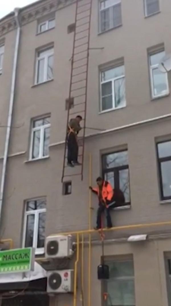 莫斯科两工人爬梯子清理积雪遭遇梯子断裂