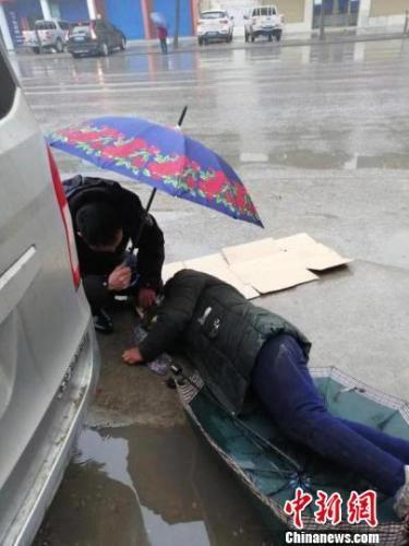 老人摔倒 民警跪地撑伞为其挡雨