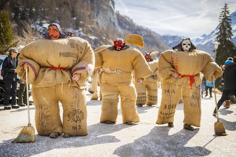 """当地时间2019年3月3日,瑞士埃沃莱纳,民众身穿装满稻草的麻袋装扮成""""稻草人"""",戴着魔鬼面具,参加传统狂欢节大游行活动。"""