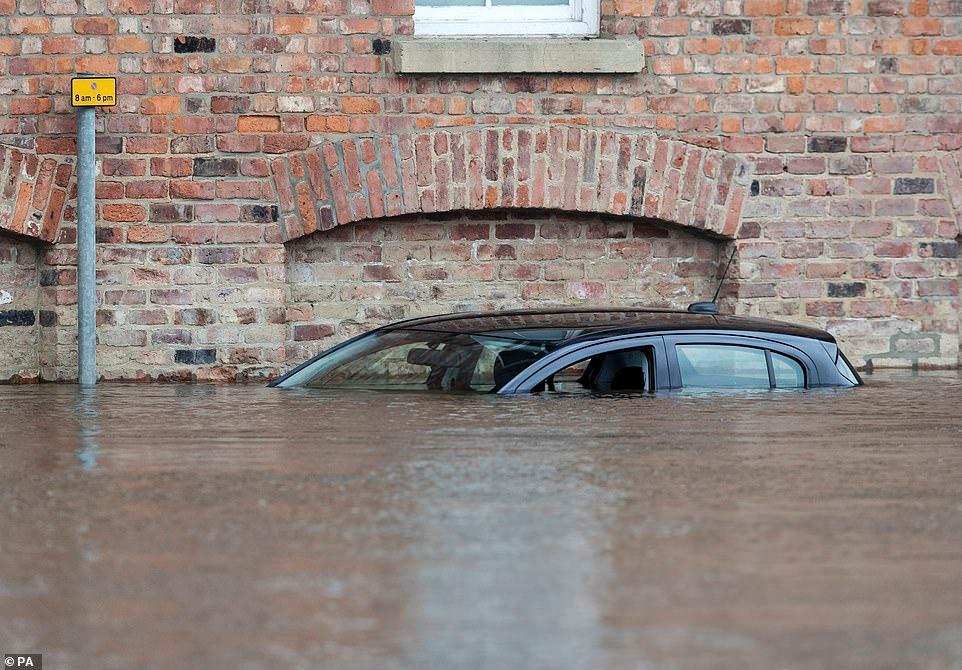 英国约克郡遭遇洪涝:道路积水齐腰深 民众水中淡定骑行