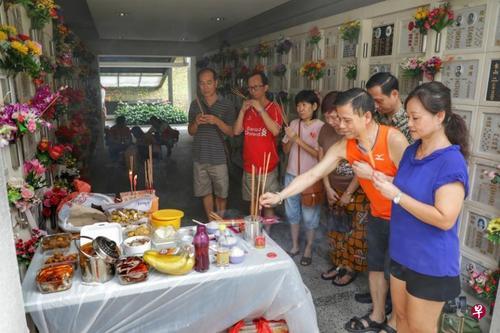 中国侨网郑利芳(右一)和她的家人每年都会依照潮州人的习俗准备供品,同时自备桌子,以便在祭拜时能摆放供品。(新加坡《联合早报》/林国明 摄)