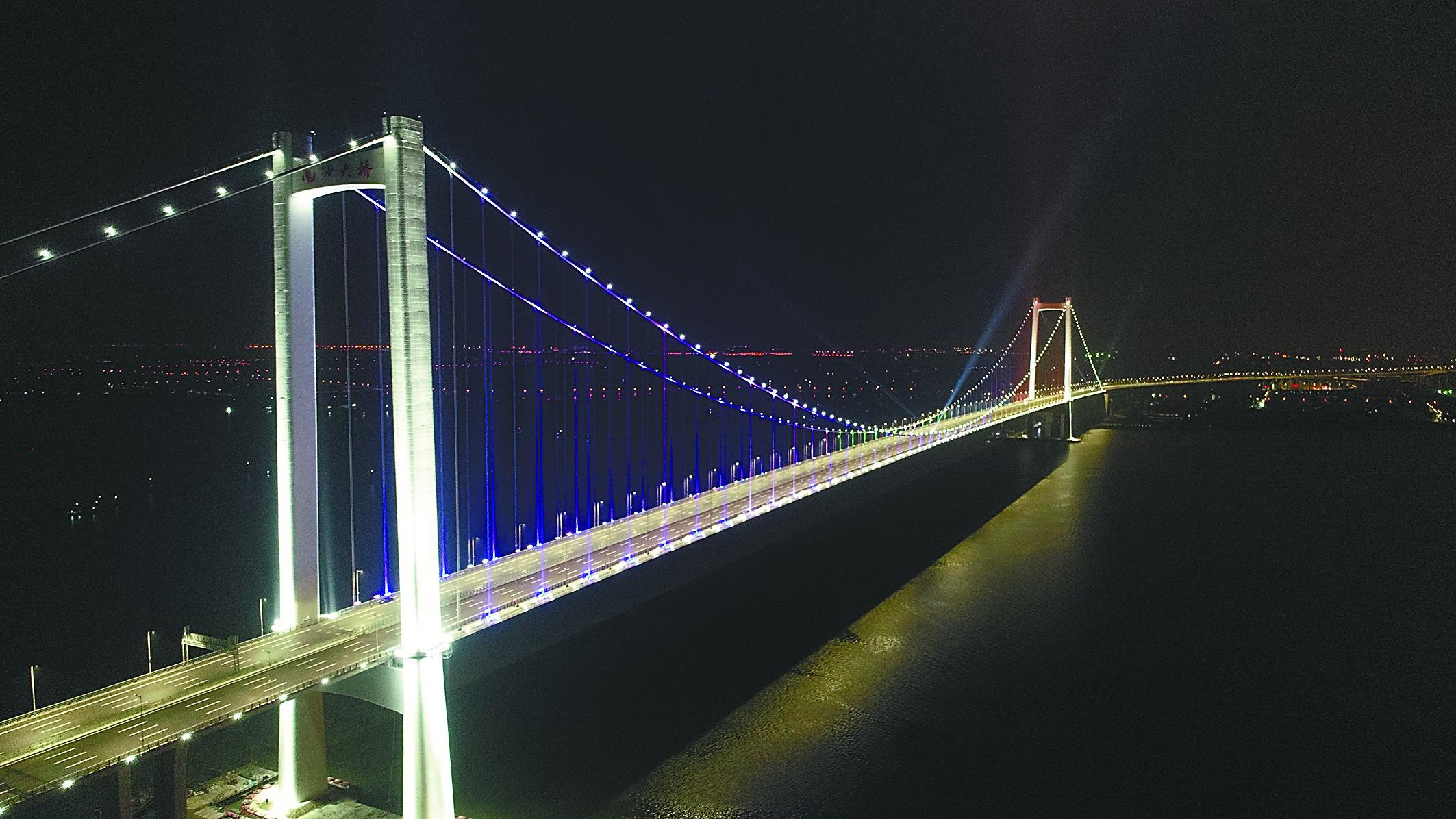 """而1688米的跨径,在目前已建成的钢箱梁悬索桥中堪称举世无双。除了跨径最长,杨敏告诉记者,虎门二桥在宽度上同样睥睨天下。""""正常的桥梁的桥面宽度在33米到35米左右,""""杨敏说,""""我们的两座悬索桥的桥面宽度达到了49.7米,桥梁双向八车道,目前为止是世界上最宽的钢箱梁悬索桥结构。""""   """"虎门二桥通车后,可以分担虎门大桥至少30%的交通量,分担黄埔大桥17%的交通量,""""杨敏说,""""并将连接起珠江东西两岸的京珠、平南、沿江、莞"""