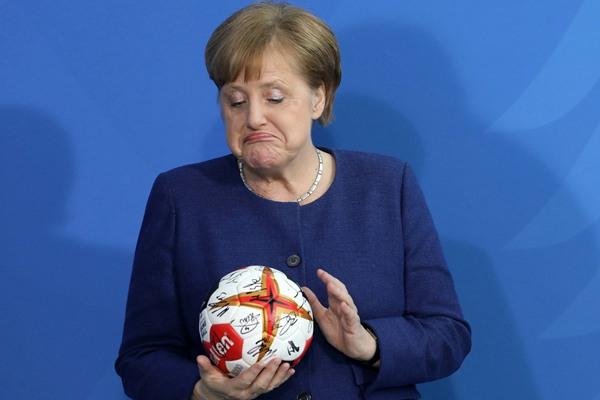 德国总理默克尔获赠手球 噘嘴表情搞怪