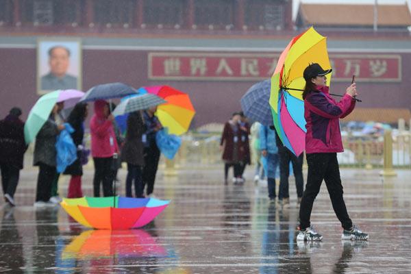 北京春雨降温 游客雨中游天安门