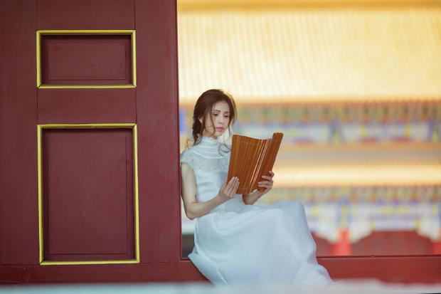 李若彤身着白裙姿态曼妙 手捧竹简展清新气质