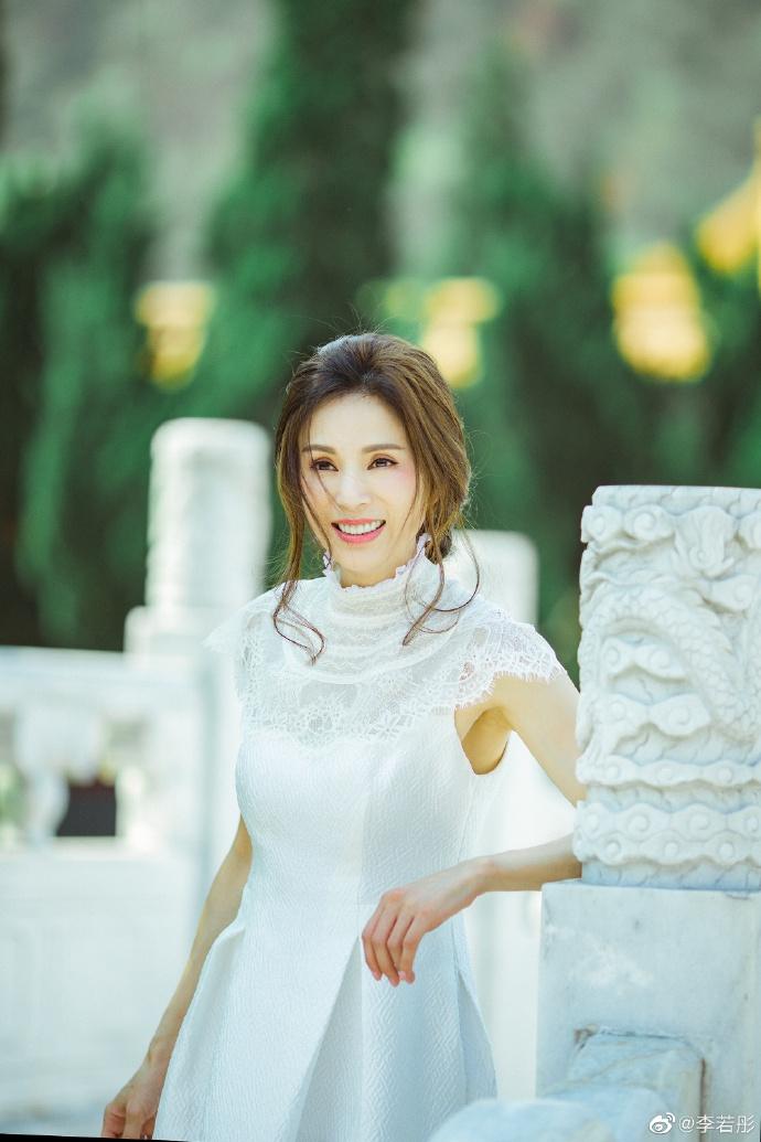 李若彤一袭白裙漫游宫廷 手持鲜花低头阅读娇媚动人