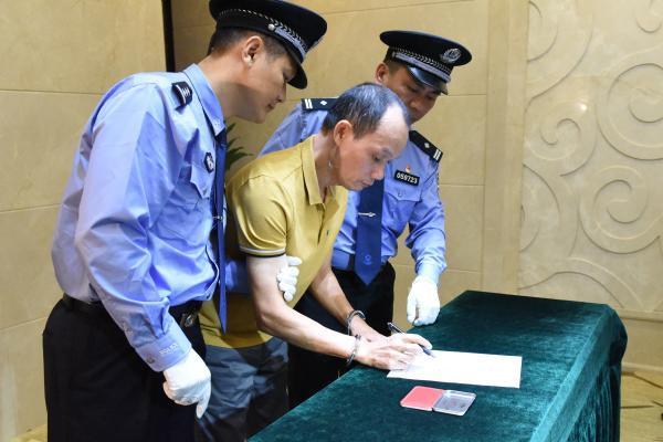 """6-""""红通人员""""梁泽宁在逮捕证上签字(深圳市纪委监委 倪勋 摄).JPG"""