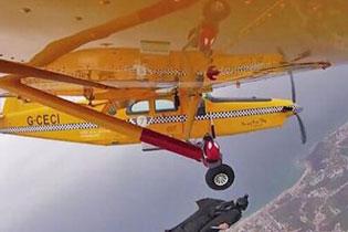 葡萄牙跳伞员爬出飞机外接翼装飞行者手中香蕉