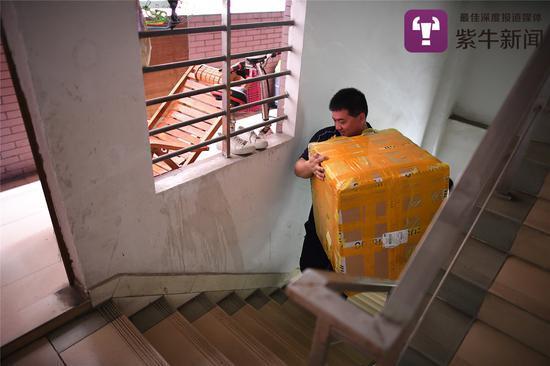 樓梯狹小,貨物體積大。張軍延必須小心地抱著貨物,以免碰撞。