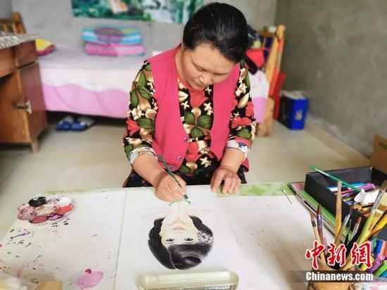 丁春梅在家中画铅笔画。赵晓 摄