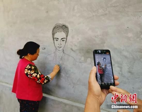 丁春梅平常画画时,丈夫会在一旁为她拍摄视频。赵晓 摄