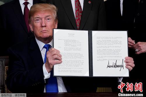 """资料图:当地时间2018年3月22日,美国总统特朗普在华盛顿签署总统备忘录,依据""""301调查""""结果,将对从中国进口的商品大规模征收关税,并限制中国企业对美投资并购。"""