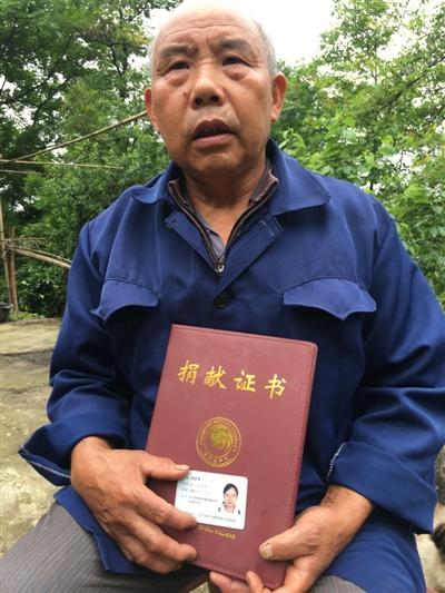 杨正贵怀抱女儿的身份证和捐献证书
