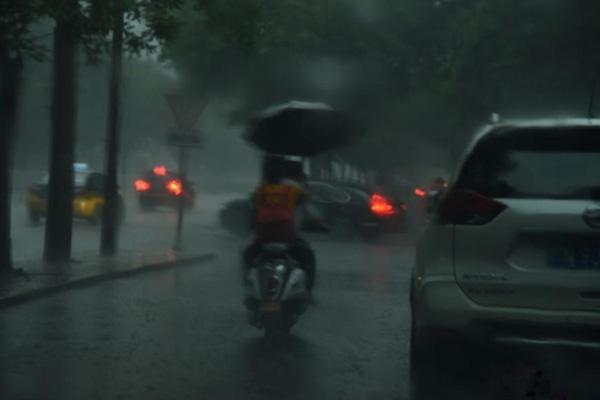 北京迎来降雨天气 民众冒雨出行
