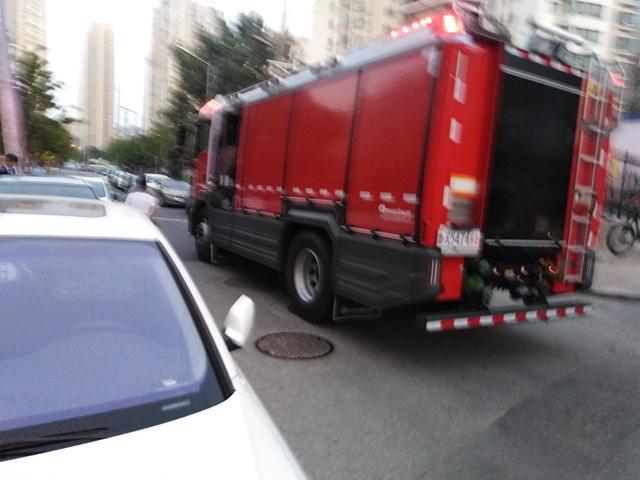 青岛永吉路一汽修厂起火,一女性伤者被救护车送医