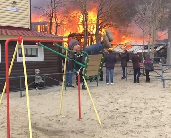 俄男孩身后房屋起火仍淡定荡秋千引起网友热议