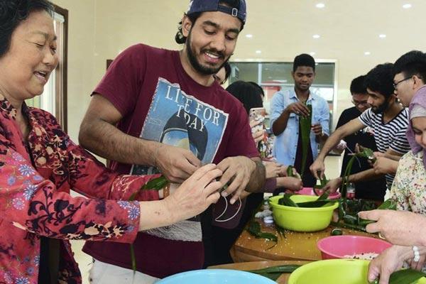 多彩活动迎端午 留学生体验包粽子制作香囊