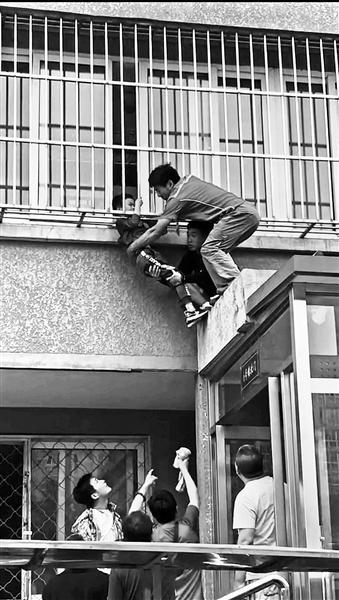 男童头卡二楼防护窗身体悬空