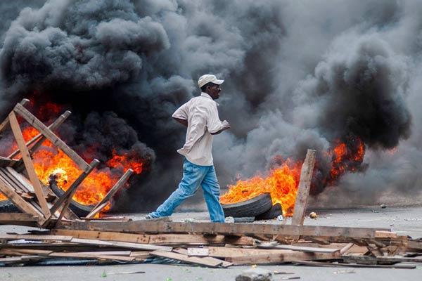 海地民众持续示威要求总统辞职 街头浓烟滚滚