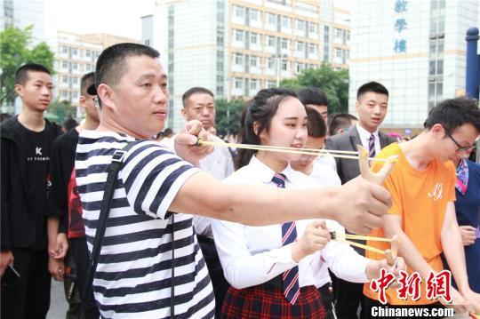 父亲在女儿的陪伴下玩起了弹弓。 钟欣 摄