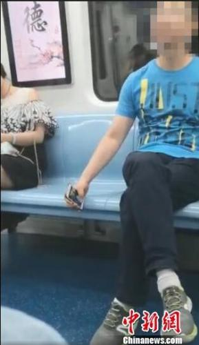 男子地铁车厢内偷拍女性隐私部位。截图 阿琳娜 摄