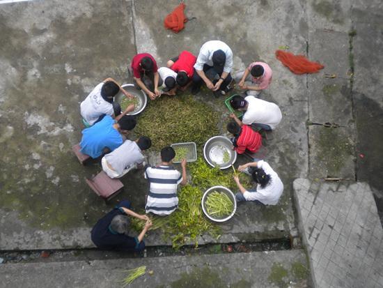 何兴武夫妇买回便宜的一包烂菜和一包烂豆,师生们围在一起挑拣。彭海惠/供图
