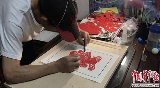 余希建在刻纸画。本版照片除署名外均为中国青年报·中青在线记者马宇平/摄
