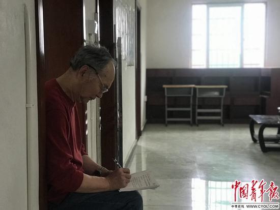 何兴武坐在教室后听年轻教师讲课。