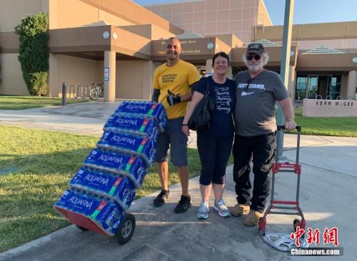 来自河滨郡的雪莉?费尔登(Sherie Ferdon,中)及其丈夫(右)驱车120多英里,到里奇克莱斯特市的救助站捐赠饮用水。中新社记者 张朔 摄