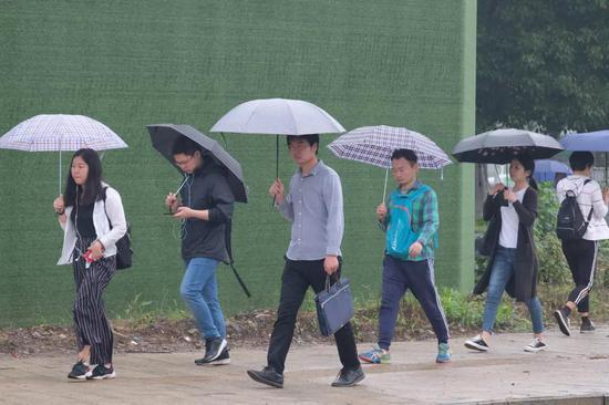 2019年5月19日,武汉一高校考点,参加2019湖北省事业单位公开招聘工作笔试的考生冒雨赶考。