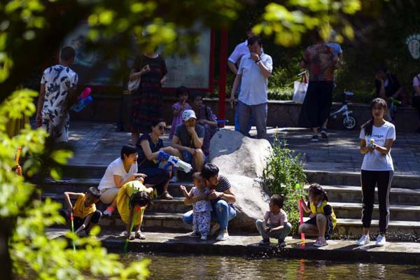 乌鲁木齐民众观鱼戏水享清凉