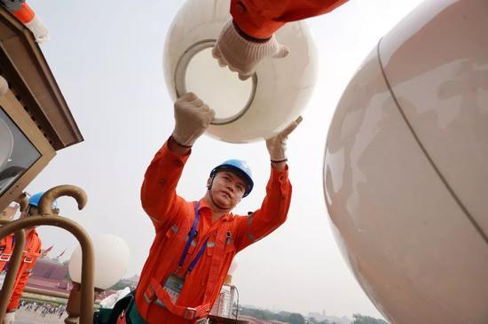 2019年6月19日,工人在酷暑中清洗检修北京天安门广场的华灯。