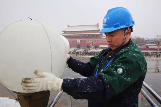 华灯班雪天巡视广场检修华灯。