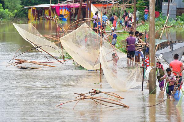 印度多地持续暴雨 居民在洪水中撒网捞鱼