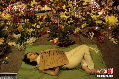图四:资料图:当地时间7月17日,乌克兰基辅,民众们手持鲜花和蜡烛在荷兰驻乌大使馆前悼念马航MH17事故遇难者。