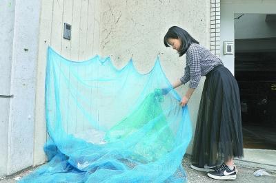 7月5日,在日本东京涩谷区惠比寿三丁目区域内,一名居民将该公寓积攒的矿泉水瓶放到垃圾回收指定地点。当日是周五,是该区域回收资源垃圾的日子。新华社记者杜潇逸摄