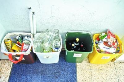 7月10日,在奥地利维也纳,当地居民勒布纳在家门口对各类包装盒和瓶装垃圾进行分类。勒布纳说,一般奥地利人会事先根据垃圾点的分类,在家中设置不同垃圾桶分别收纳垃圾,方便在垃圾点分类丢弃。 新华社记者郭晨摄