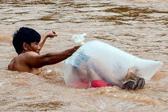 越南河流洪水泛滥 家长用塑料袋运孩子过河上学