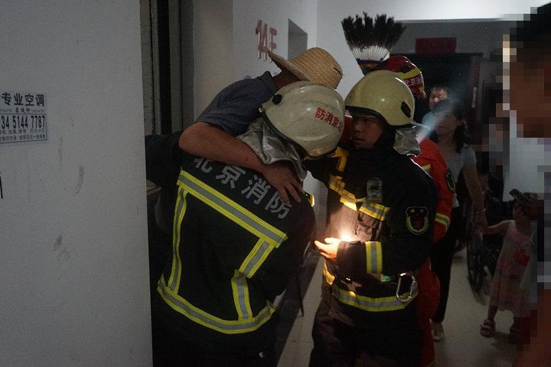 消防员救被困老人 邻居为消防员扇风降温