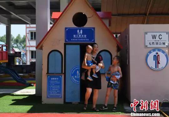 """图为一市民带着两个小孩在""""第三更衣室""""换衣服。陈超 摄"""