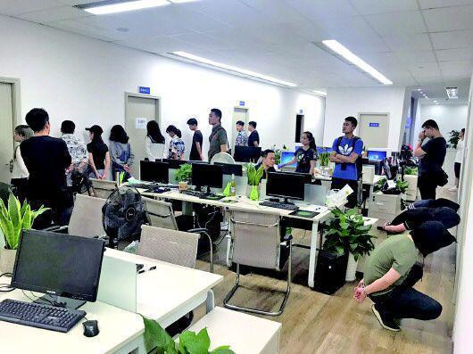 专案组民警突袭位于长沙某写字楼的诈骗公司。   (警方供图)