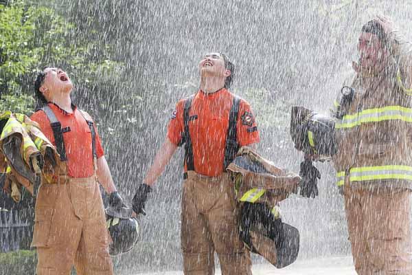 高温难耐 韩国消防员路边冲凉消暑