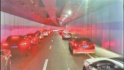 私家车贴近隧道墙壁避让消防车
