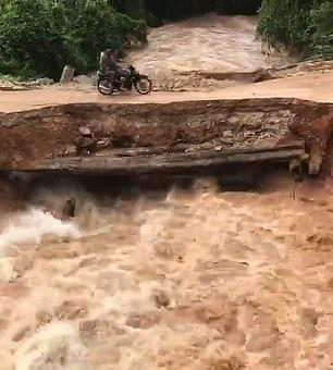 柬埔寨一处桥梁被洪水冲塌 两名骑车男子落水
