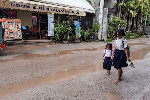 柬埔寨暹粒雨中街头 女学生怕湿鞋光脚走泥路