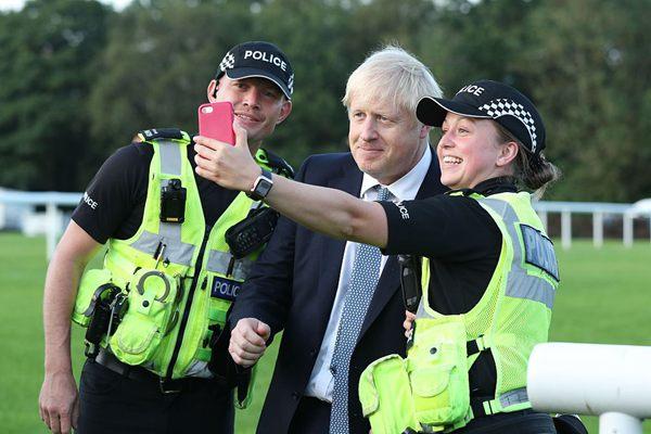 英国首相?#24049;?#36874;探访大坝受损地区 与救援人员玩自拍